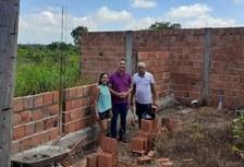 Pra cego ver: Coordenadores e presidente da associação no terreno da futura sede. As paredes da construção estão sendo levantadas e eles estão na frente dessa edificação. Fim da descrição.