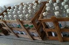 Pra cego ver: Galões de álcool em gel colocados em caixotes para entrega. Fim da descrição.