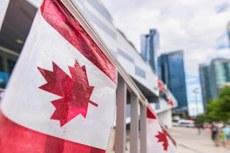 Pra cego ver: Bandeira do Canadá, pendurada no mastro, em primeiro plano. E ao fundo, prédios grandes e espelhados.