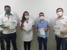 Pra cego ver: Quatro pessoas posando, dois professores do IFTO e dois servidores do hospital. Cada um segurando uma máscara de proteção no estilo face shield. Entrega no Hospital de Doenças Tropicais (HDT), em Araguaína.
