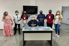 Na imagem, coordenador e estudantes participantes da Spatron Robótica, diretor-geral da unidade de Porto Nacional e servidores do Tribunal de Justiça durante a entrega do primeiro lote de máscaras faciais