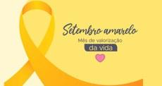 """Ilustração de um laço de fita da cor amarela. Com o texto """"Setembro Amarelo. Mês de valorização da vida."""" Ilustração representativa de um coração. Fim da descrição."""