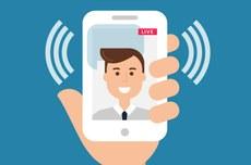 """Pra cego ver: ícone representativo de uma mão segurando um telefone celular, com o rosto de uma pessoa ao fundo da tela, e ao lado escrito a palavra """"live""""com o símbolo representativo de transmissão. Fim da Descrição."""