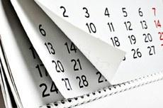 Pra cego ver: imagem representativa de um calendário com várias folhas e datas impressas no papel. Fim da descrição.