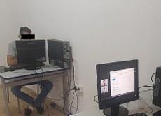 Pra cego ver: Estudante apenado em frente ao computador, no centro para monitorados. Fim da descrição.